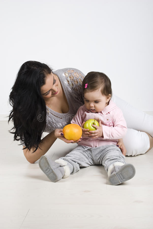 Mother giving fruits to her little baby. Young mother sitting on wooden floor with her baby girl , giving her child fruits and teaching,check also in this stock images