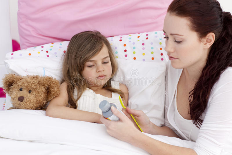 Mother Giving Her Daughter Cough Medicine Stock Photo