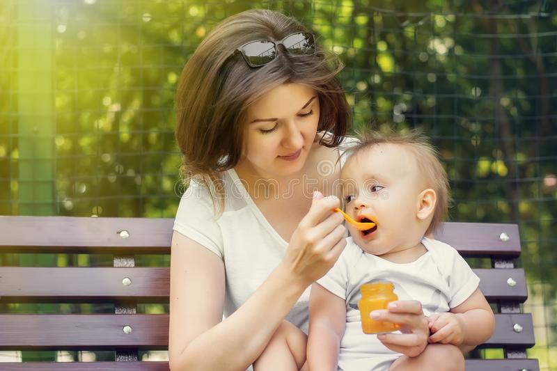 Mother giving her infant child complementary feeding pumpkin puree in sunny day outdoor. Both mom and kid sit on bench in park royalty free stock images