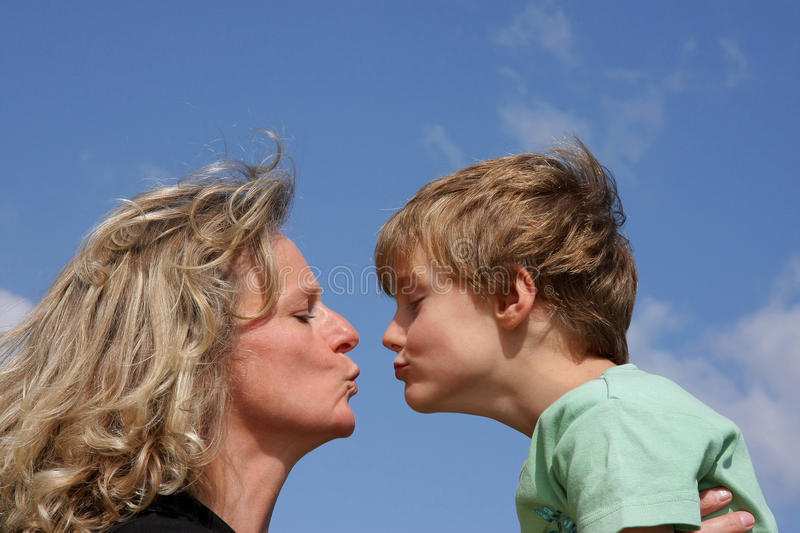 A Mother Giving Her Son A Kiss Stock Image - Image of