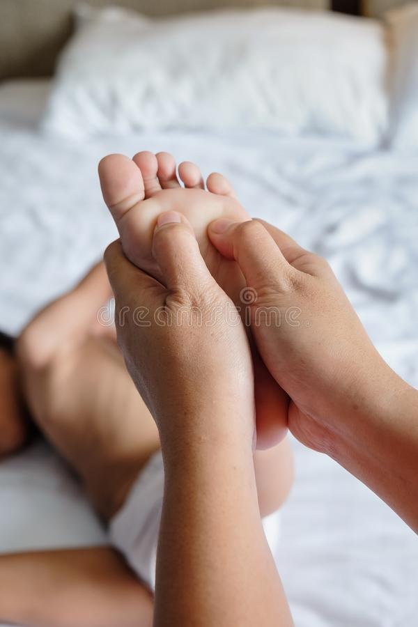 Mother Giving Kid Foot Therapy Massage To Stimulate His Growth stock image