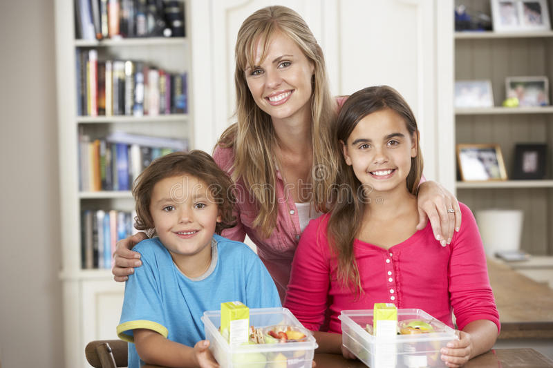 Mother Giving Two Children Healthy Lunchboxes In Kitchen stock photos
