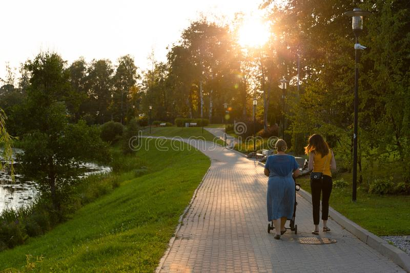 Mother and grandmother with a child in a stroller with walking in a park having quality family time. In a natural light stock photos