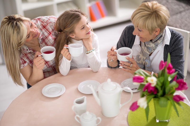 Mother, grandmother and daughter together on tea party royalty free stock image