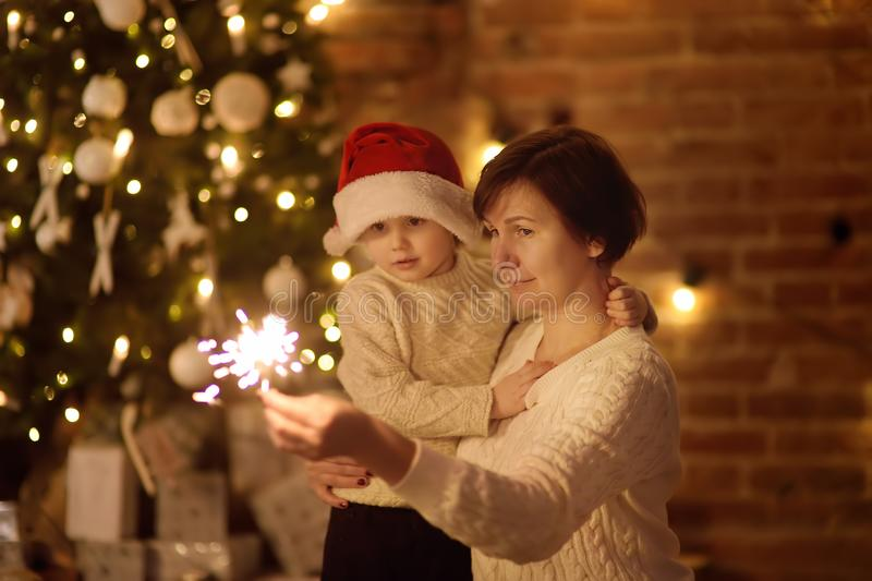 Mother or grandmother with her little son or grandson celebration Christmas with sparkler. In cozy living room in winter stock photo