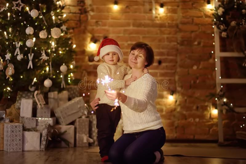 Mother or grandmother with her little son or grandson celebration Christmas with sparkler. In cozy living room in winter stock photography