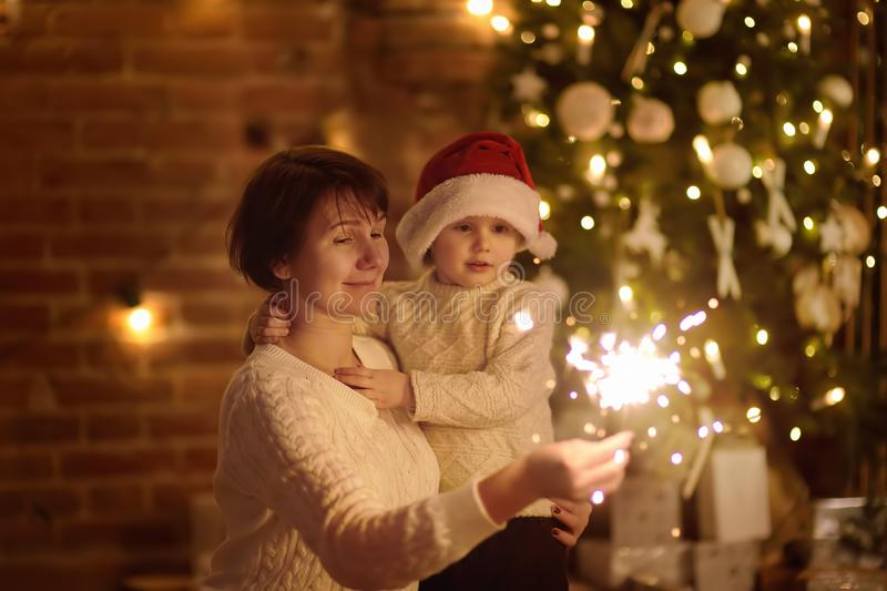 Mother or grandmother with her little son or grandson celebration Christmas with sparkler. In cozy living room in winter stock images