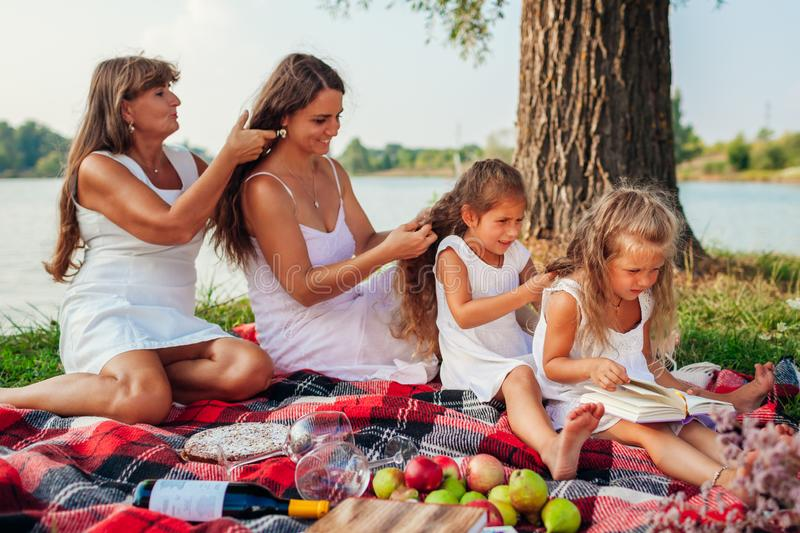 Mother, grandmother and kids weaving braids to each other. Family having fun during picnic in park. Three denerations stock image