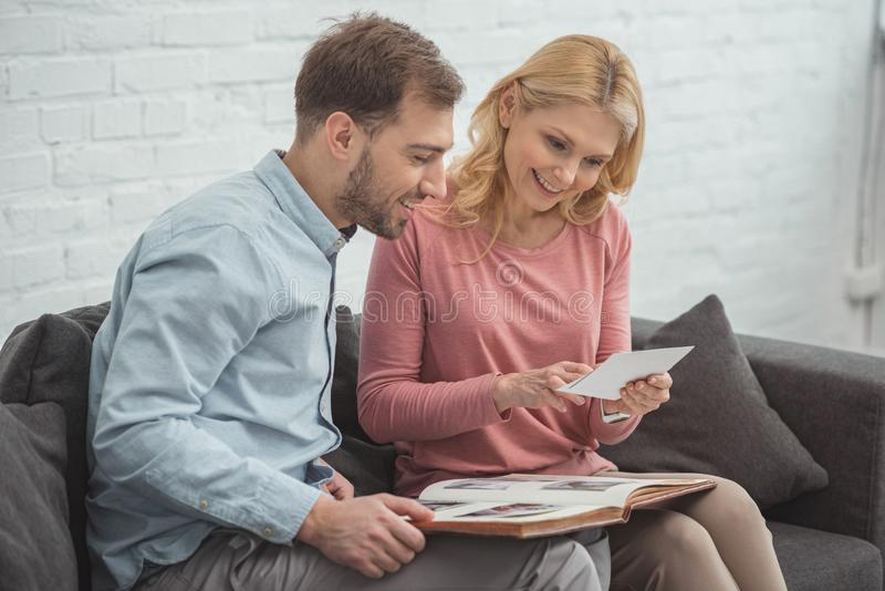 mother and grown son looking at photo in hand while resting stock image