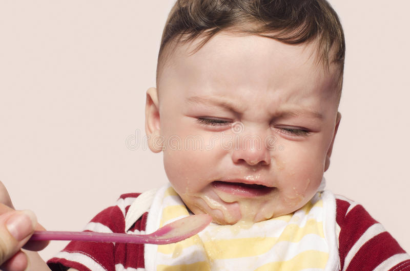 Mother hand feeding food to baby crying. royalty free stock photos
