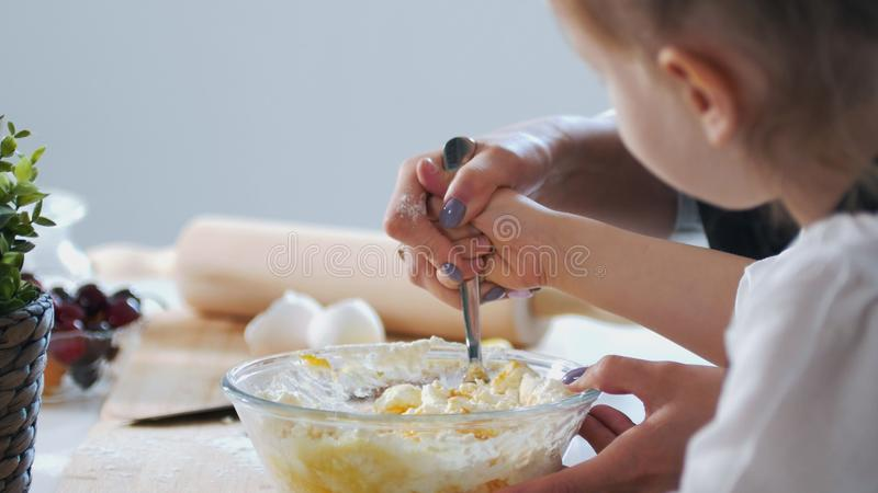 Mother hand with her child mixing the dough for preparing pancakes stock photography