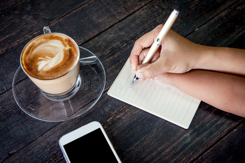 Mother hand holding child hand writing on notebook. Over wooden table with coffee cup and cellphone stock photography