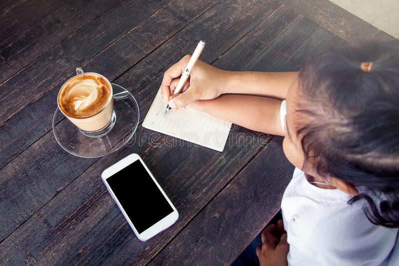 Mother hand holding child hand writing on notebook. Over wooden table with coffee cup and cellphone stock image