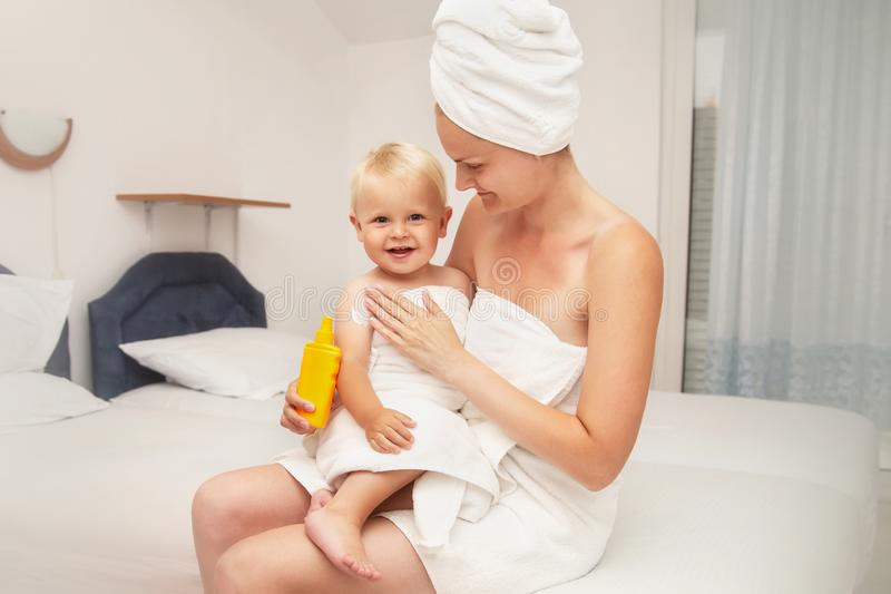 Mother and happy infant baby in white towels after bathing apply sunscreen or after sun lotion. Children skin care in a hotel or. Bedroom. Spf, skin moisturizer royalty free stock photography