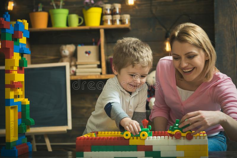 Mother and happy son play with constructor. Motherhood concept. Nursery with toys and chalkboard on background. Family. Playing with constructor at home. Mother royalty free stock image