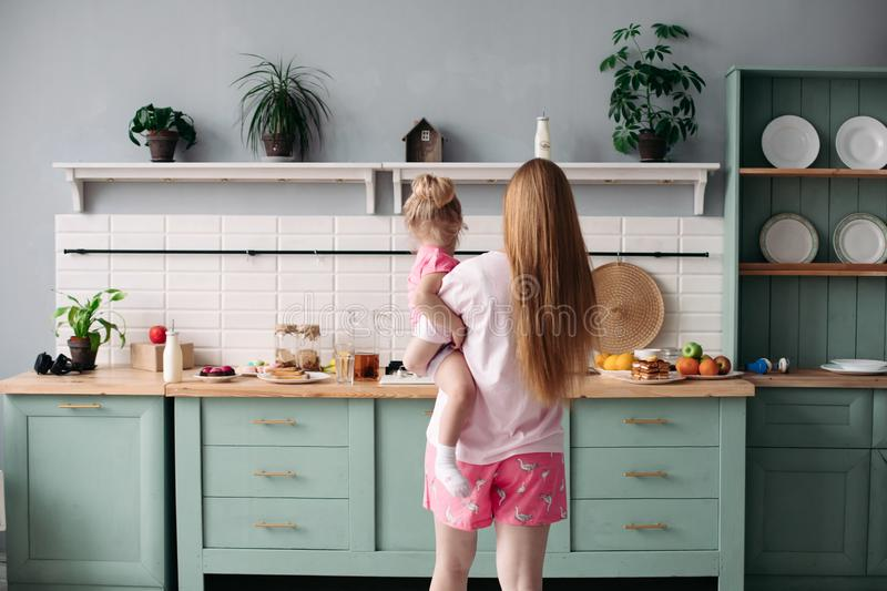 Mother having breakfast with her lovely daughter in the kitchen. stock photography