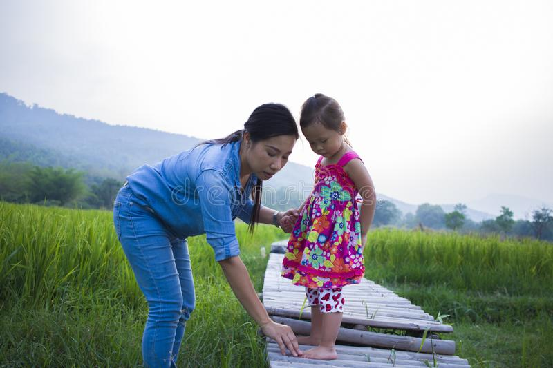 Mother help her child to cross stream, mother lifting daughter in rice field royalty free stock photography