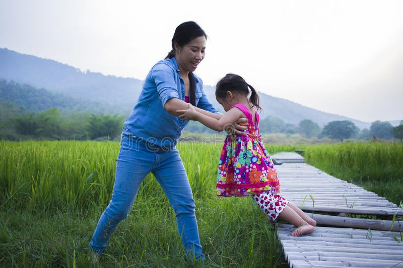 Mother help her child to cross stream, mother lifting daughter in rice field stock photo