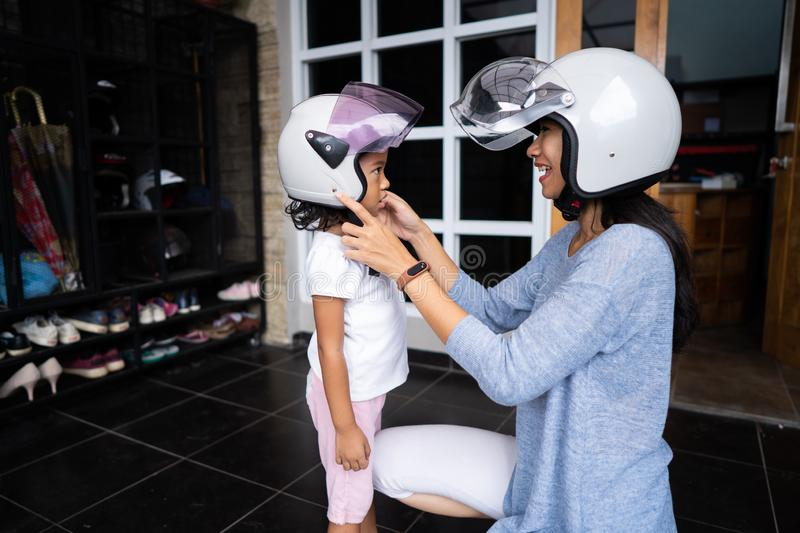 Mother help her child to put on a helmet royalty free stock image