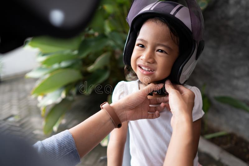 Mother help her child to put on a helmet royalty free stock photo