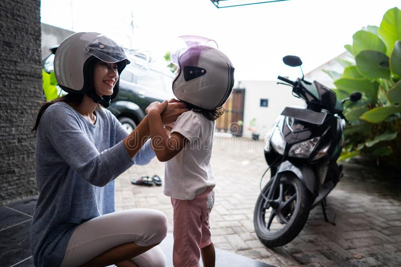 Mother help her child to put on a helmet royalty free stock photos