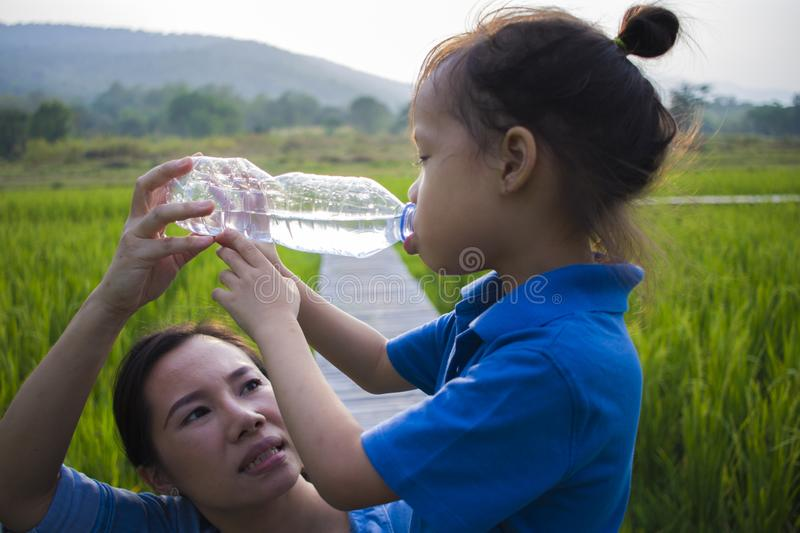 Mother help her children drinking water from bottle in rice field. long hair boy stock photography