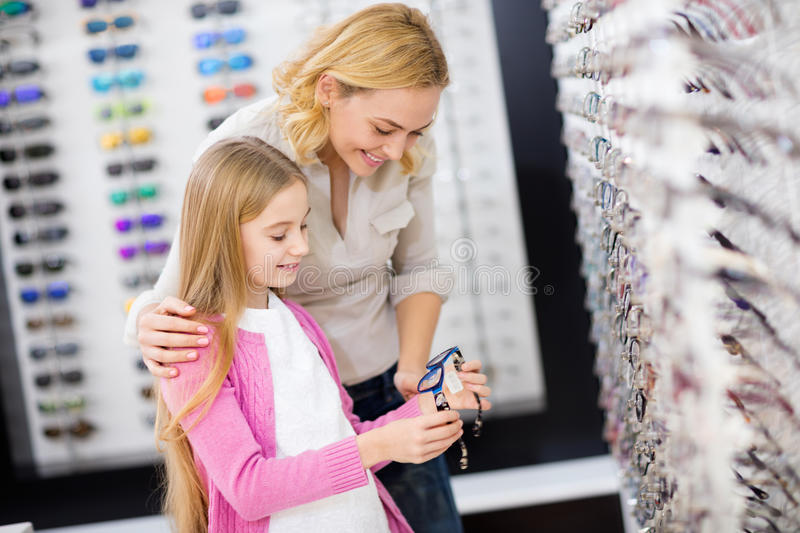 Mother help her girl to choose good frame for eyeglasses stock photos
