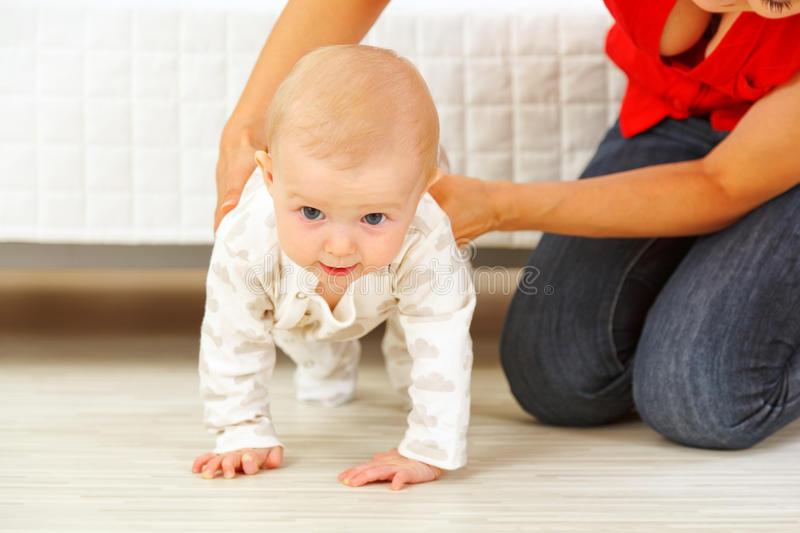 Mother Helping Cheerful Baby Learn To Creep Stock Photo