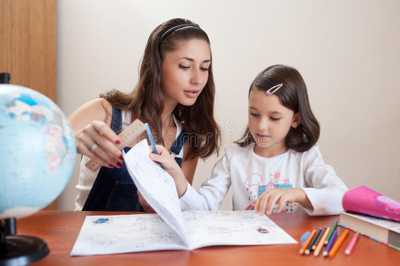 Mother helping daughter do homework stock photography