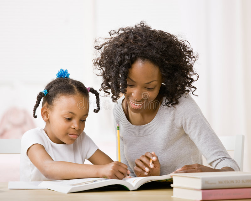Download Mother Helping Daughter Do Homework In Workbook Stock Image - Image: 6602989