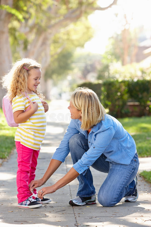 mother helping daughter tie shoe laces on walk to school stock image