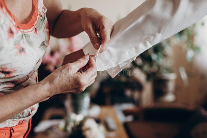 Mother helping groom putting on cuff links, getting ready in the royalty free stock images