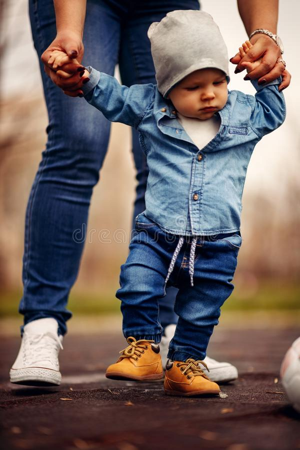 Mother is helping her boy taking his first steps stock image