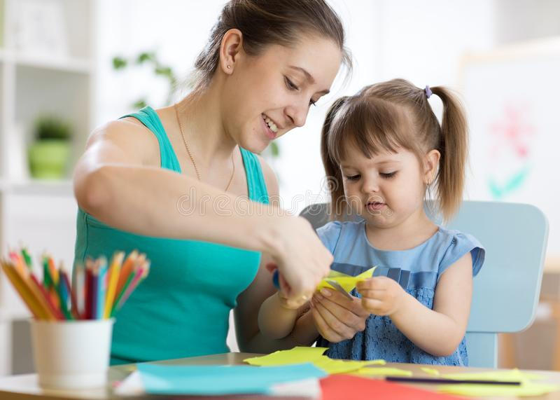 Mother helping her child to cut colored paper royalty free stock photo