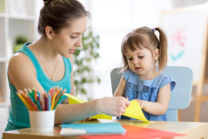 Mother helping her child to cut colored paper stock photos