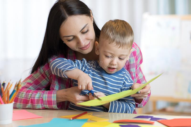 Mother helping her child to cut colored paper stock photography