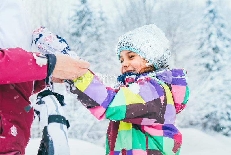 Mother helping her little daughter wearing warm gloves during snowy forest walking royalty free stock photo