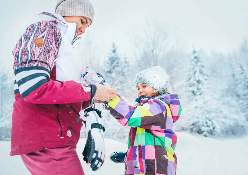Mother helping her little daughter wearing warm gloves during snowy forest walking royalty free stock image