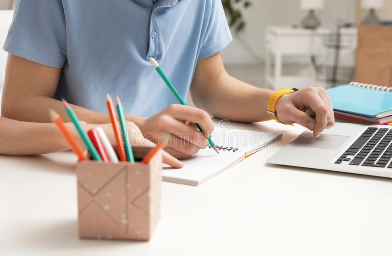 Mother helping her teenager son with homework at desk. Closeup royalty free stock images