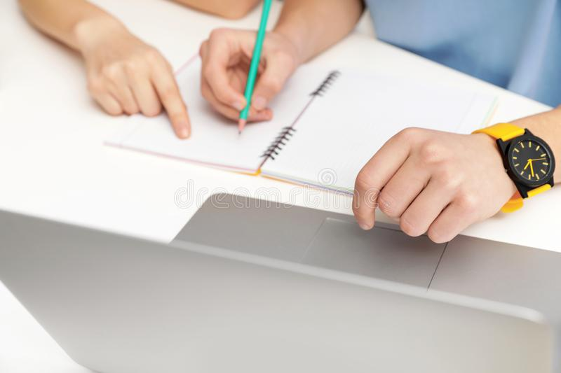 Mother helping her teenager son with homework at desk. Closeup stock photography