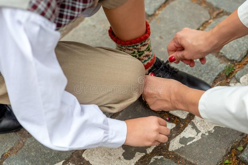 Mother is helping his son to tie his shoes before the concert. royalty free stock images