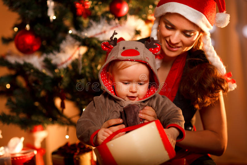 Mother helping interested baby open present box