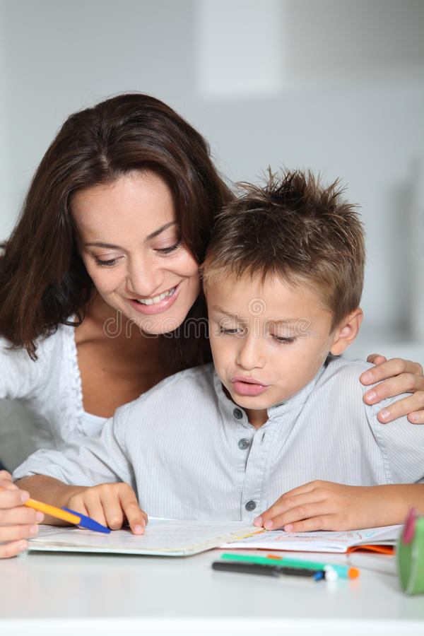 Mother Helping Son In Reading Royalty Free Stock Photos