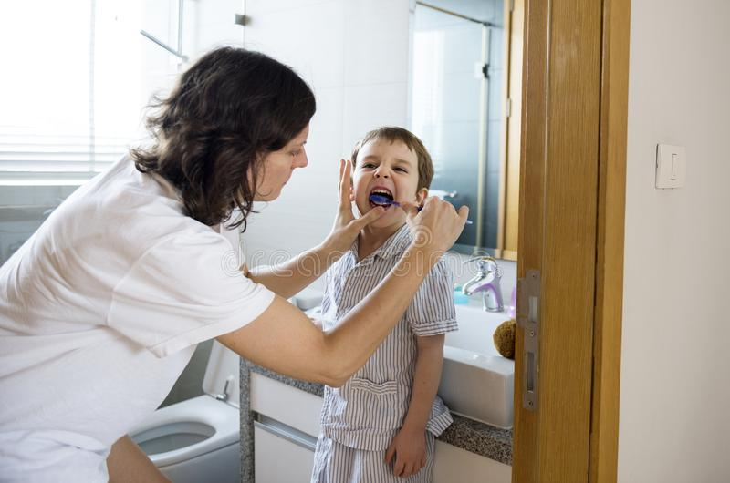 Mother helping son to brush his teeth royalty free stock images