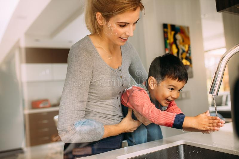 Mother helping son to wash hands after baking stock images