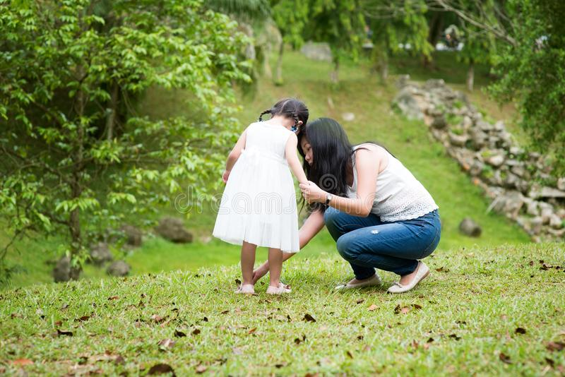 Mother helps little girl wearing shoe royalty free stock photography
