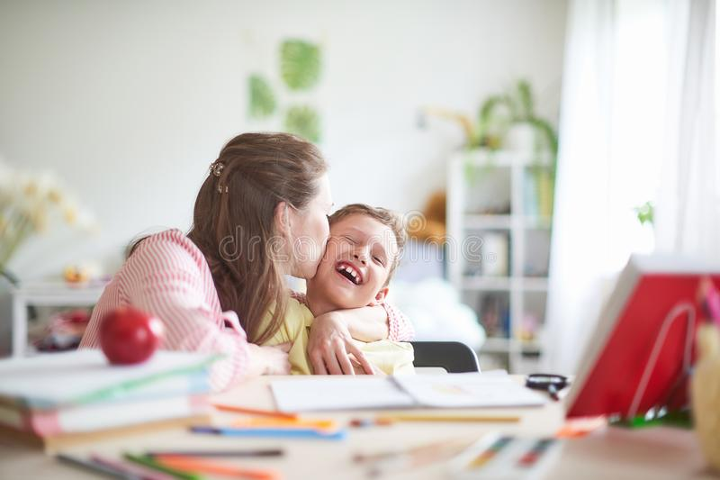 Mother helps son to do lessons. home schooling, home lessons. the mother deals with the child, checks the job done. outside school royalty free stock photo