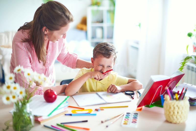 Mother helps son to do lessons. home schooling, home lessons. the tutor is engaged with the child, teaches to write and count stock images