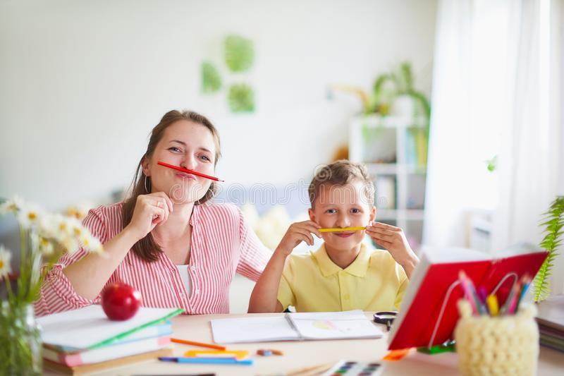 Mother helps son to do lessons. home schooling, home lessons. the woman is engaged with the child, checks the job done. outside royalty free stock images