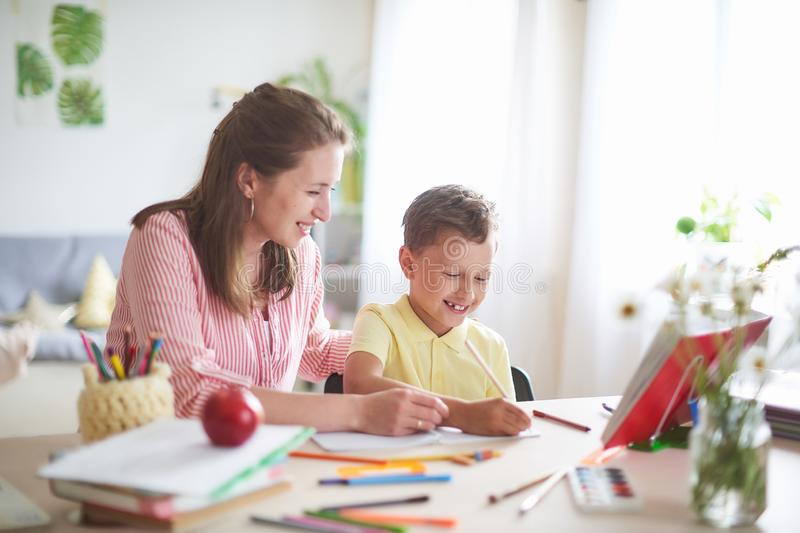 Mother helps son to do lessons. home schooling, home lessons. the tutor is engaged with the child, teaches to write and count. out. Of-school lessons with a royalty free stock photo